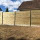 Photo d'une clôture avec des lames de bois emboitées, plaques de soubassement béton et poteaux aluminium